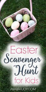 pink basket of Easter eggs sitting on the grass