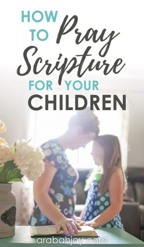 mother and daughter stand facing each other in a posture of prayer with their foreheads touching, eyes closed, and hands on an open Bible